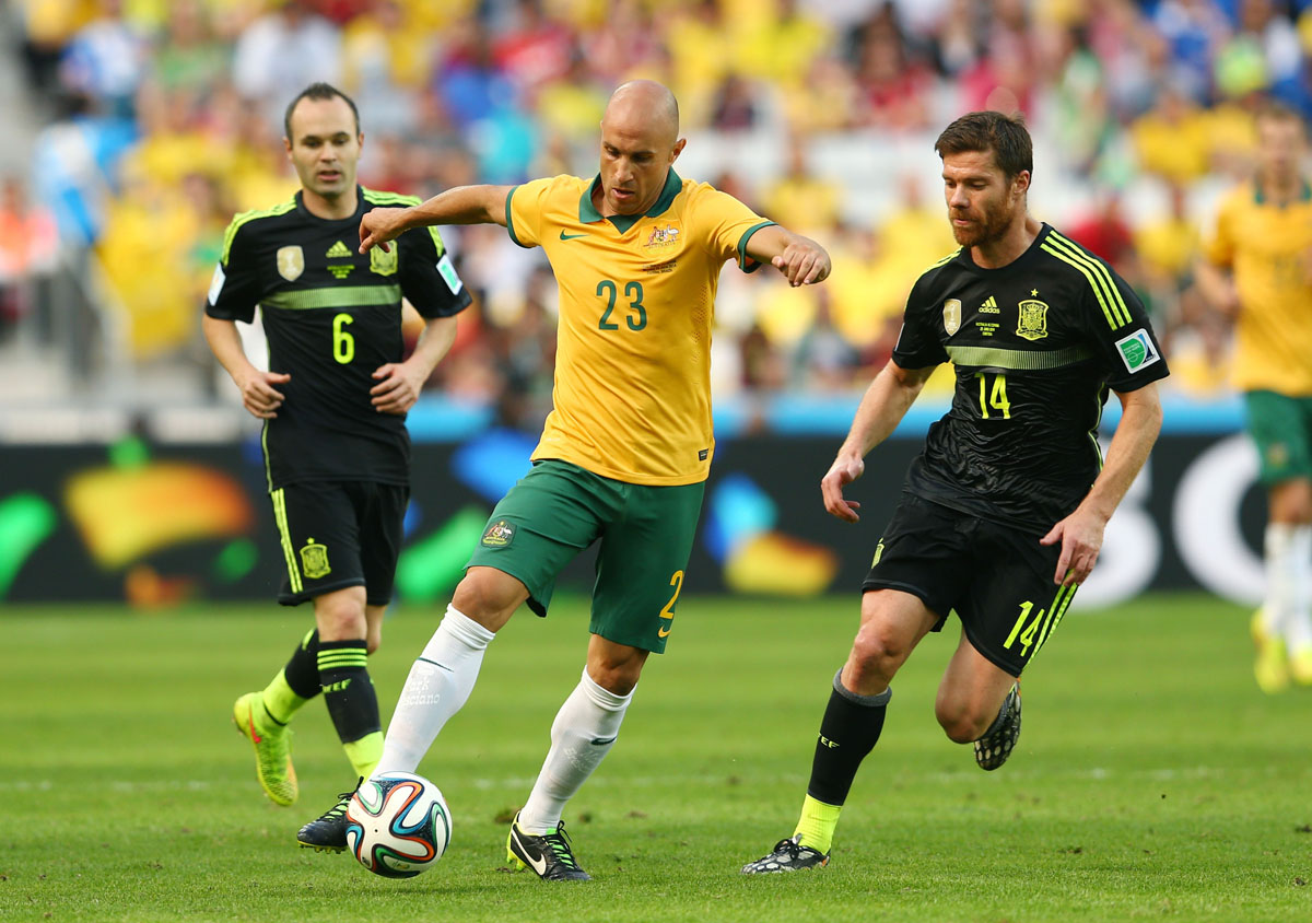 CURITIBA, BRAZIL - JUNE 23:  Mark Bresciano of Australia controls the ball against Andres Iniesta (L) and Xabi Alonso of Spain during the 2014 FIFA World Cup Brazil Group B match between Australia and Spain at Arena da Baixada on June 23, 2014 in Curitiba, Brazil.  (Photo by Cameron Spencer/Getty Images) ORG XMIT: 491933361